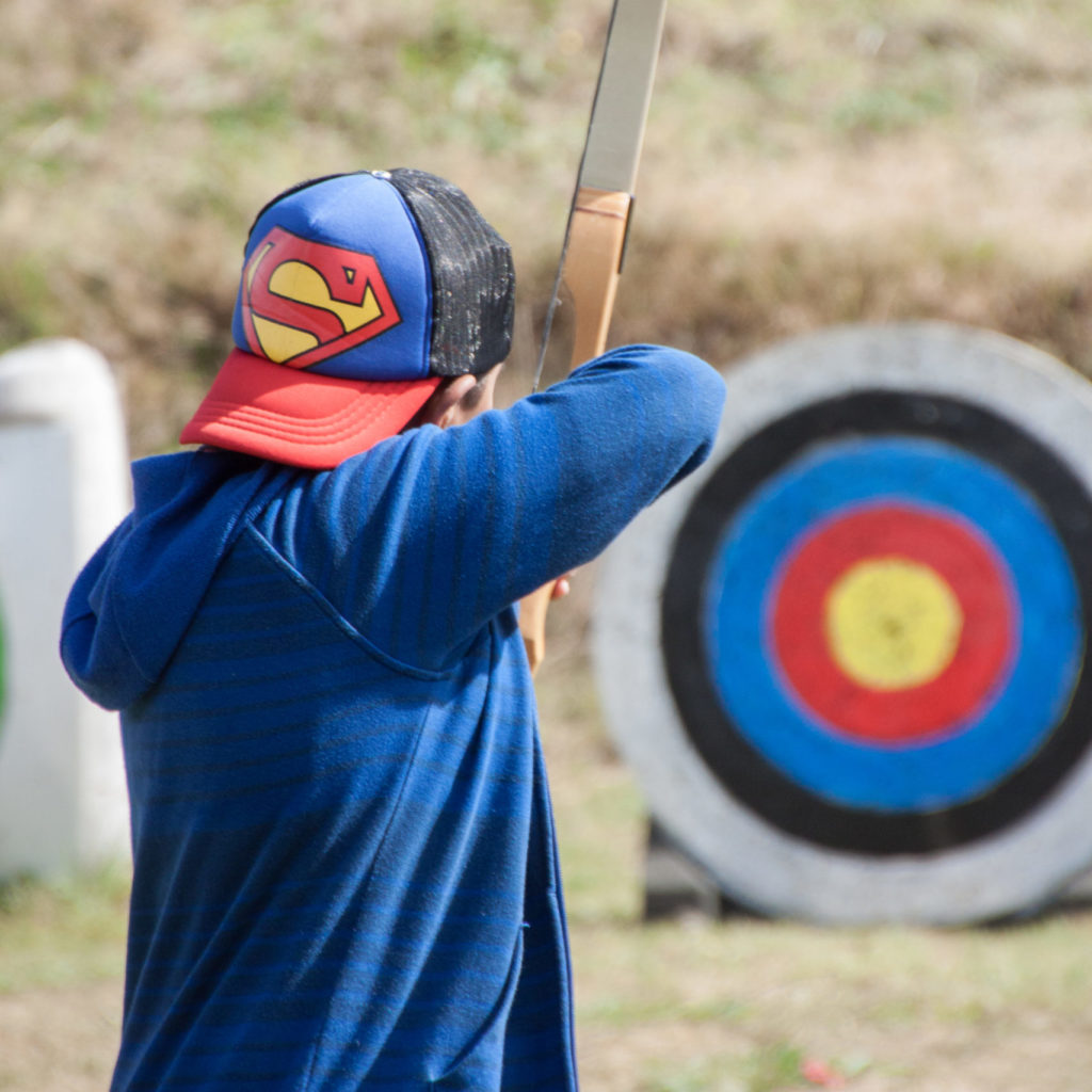 Student learning archery as part of a camp programme